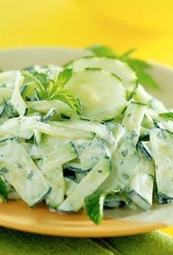 Салат из свежих огурцов, листового салата и зеленого лука со сметаной
